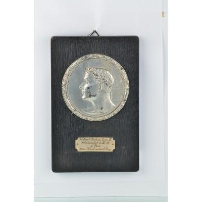 Srebrzona plakieta nagrodowa z zawodów pływackich zamontowana na drewnianej płycie, 1936r.